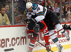 February 20, 2008; Newark, NJ, USA; New Jersey Devils defenseman Johnny Oduya (29) is hit by San Jose Sharks center Joe Thornton (19) during the first period at the Prudential Center in Newark, NJ.