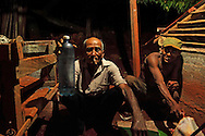 Offering a bottle of rum near La Maquina, Guantanamo, Guantanamo, Cuba.