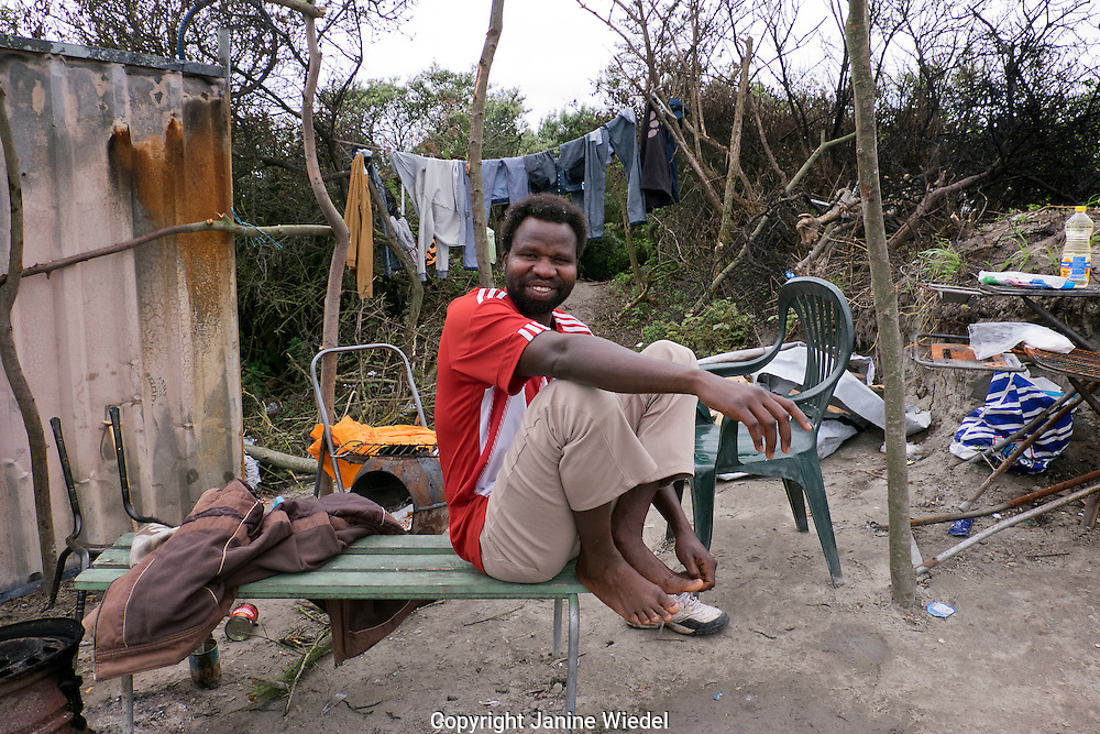 Refugee from Darfour Sudan drying his newly washed feet. The Calais Jungle Refugee and Migrant Camp in France