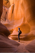 Woman hiker in Canyon X, a slot canyon on the Navajo Reservation near Page, Arizona.