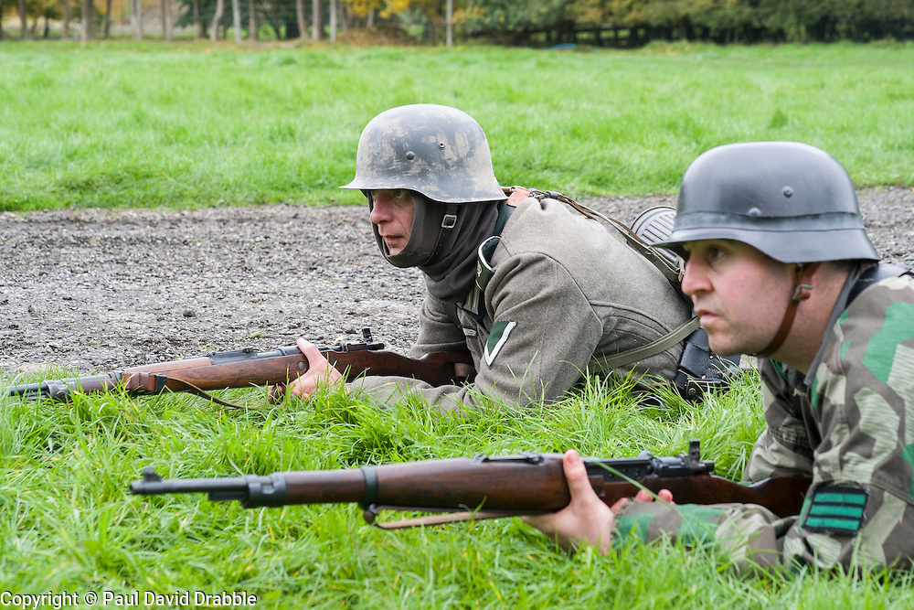 Re-enactors portrayiing German panzer grenadiers from the Gro&szlig;deutschland Division. both are wearing the iconic Steel Helmet. The man on the left has a gefreiter rank badge on his arm. The soldier on the right is wearing a tactical rank badge of Feldwebel on his camouflage smock<br /> Pickering Showground battle reenactment 1940 war time weekend<br /> <br /> 17/18 October 2015<br />  Image &copy; Paul David Drabble <br />  www.pauldaviddrabble.co.uk
