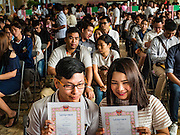 "14 FEBRUARY 2017 - BANGKOK, THAILAND:  A couple holds up their wedding registrations in the Bang Rak district in Bangkok. Bang Rak is a popular neighborhood for weddings in Bangkok because it translates as ""Village of Love."" (Bang translates as village, Rak translates as love.) Hundreds of couples get married in the district on Valentine's Day, which, despite its Catholic origins, is widely celebrated in Thailand.     PHOTO BY JACK KURTZ"