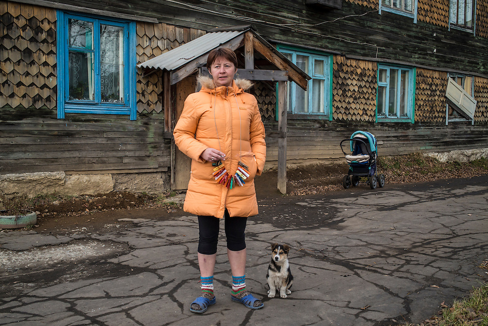 A woman stands outside her apartment building on Wednesday, October 23, 2013 in Vydrino, Russia.