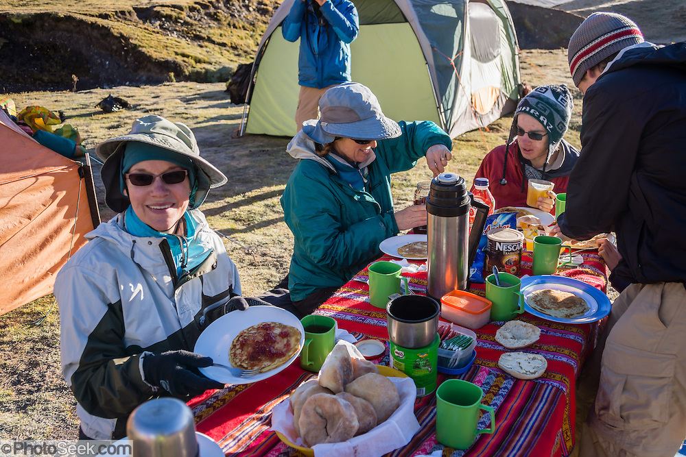 Trekkers eat a pancake breakfast in Tuctucpampa campground. Day 2 of 9 days trekking around the Cordillera Huayhuash in the Andes Mountains, Peru, South America. For licensing options, please inquire.