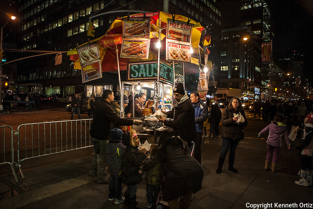 A hot dog vendor servers his waiting customers on 6th Avenue and 47th Street in New York City at night.