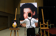 John Shaw, of Kirk Briggs Signs, removes a giant photo of Chandra Levy after the memorial service held at Centre Plaza in Modesto, California, May 28, 2002 where 1,100 mourners gathered. A few hours before Washington, D.C. police had confirmed that the former intern's death had been a homicide. Photo by Jakub Mosur