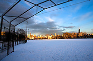 The sun briefly breaks through the low winter clouds as they roll over Chicago, IL. The baseball diamonds in Eckhart Park, on the city's near west side, lay empty on this cold and snowy day.