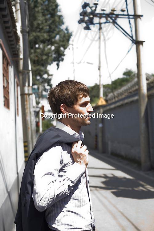 """BEIJING, AUG.3, 2012 : Stararchitekt Ole Scheeren geht durch  eine Gasse in der Naehe des Bauplatzes des """" Guardian Auction House"""" in Peking's Stadtmitte."""