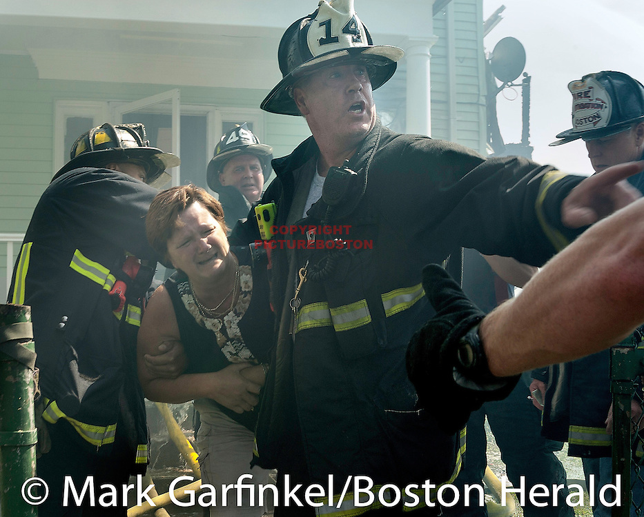 08/17/13-Boston,MA- Boston firefighters help Kathleen Kieran after she broke through fire lines to get to her childhood home, which was destroyed in a 4 alarm fire at 306 South St. in Jamaica Plain today, August 17, 2013. Staff photo by Mark Garfinkel