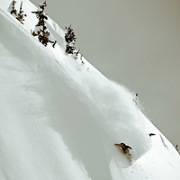 Professional snowboarder Chris Wimbles sprays some light winter snow in the Coast Mountain Range of British Columbia.
