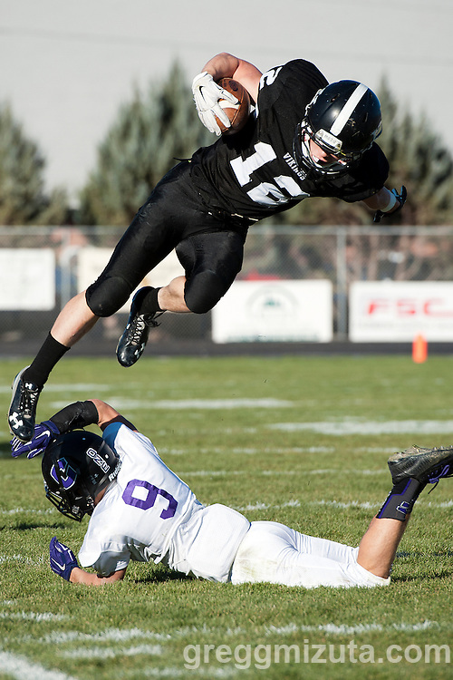 Zac Jacobs jumps over Zach Fralich during the Vale - Cascade Christian 3A quarterfinal playoff game at Frank Hawley Stadium, Vale, Oregon, Saturday, November 14, 2015. Vale won 48-38. Jacobs rushed for 196 yards and two touchdowns.