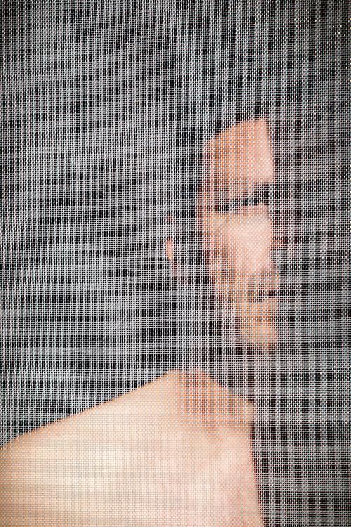 portrait of a man standing behind a screen door