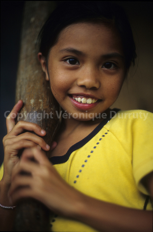 IFUGAO LITTLE GIRL PREPARING RICE IN ITS VILLAGE, CORDILLERA, LUZON ISLAND, THE PHILIPPINES