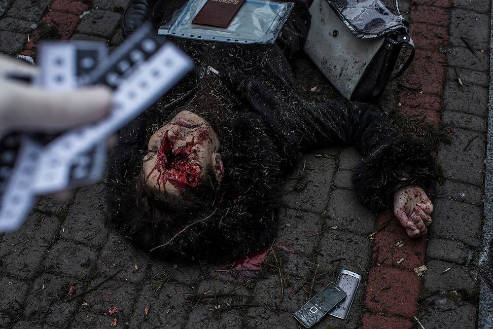 DONETSK, UKRAINE - JANUARY 30, 2015: The body of a woman killed by a rocket attack lies on the ground near a humanitarian aid distribution center in Donetsk, Ukraine. At least five people were killed at the scene, and at least two others died in a separate shelling nearby. CREDIT: Brendan Hoffman for The New York Times