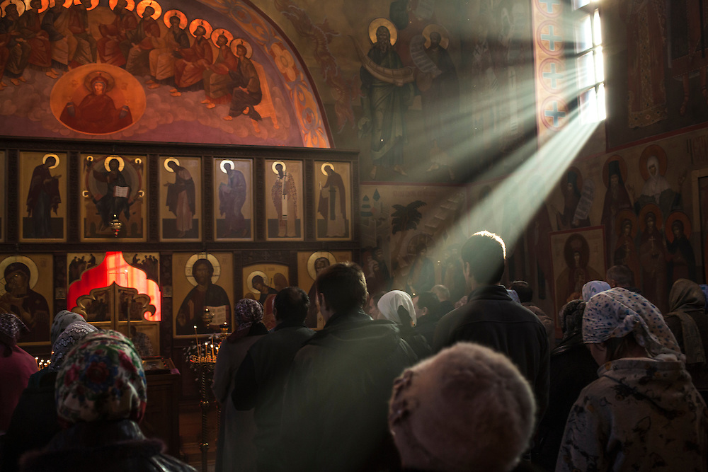 Sunlight shines through a window during a church service on Sunday, October 20, 2013 in Baikalsk, Russia.