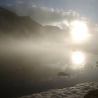 Sunrise, reflected in high altitude lake with snow on the edge of lake. Clearing summer morning storm