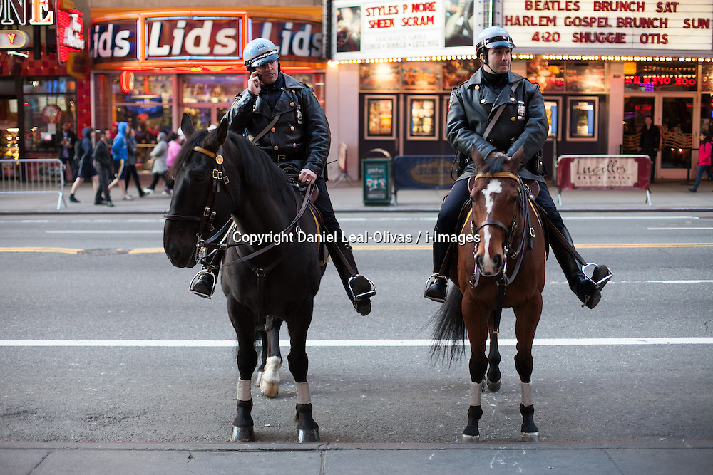 Two police officers from the NY police department mounting a horse on  42nd St close to Time sq..In response to the Boston Marathon Bombings, New York City has increased security throughout the city, including a show of presence by the NYPD in Times Square in New York,  ..Two bombs that went off near the finish line of the Boston Marathon killed three people and injured 144, USA, on April 15, 2013, April 18, 2013. Photo by: Daniel Leal-Olivas / i-Images. .
