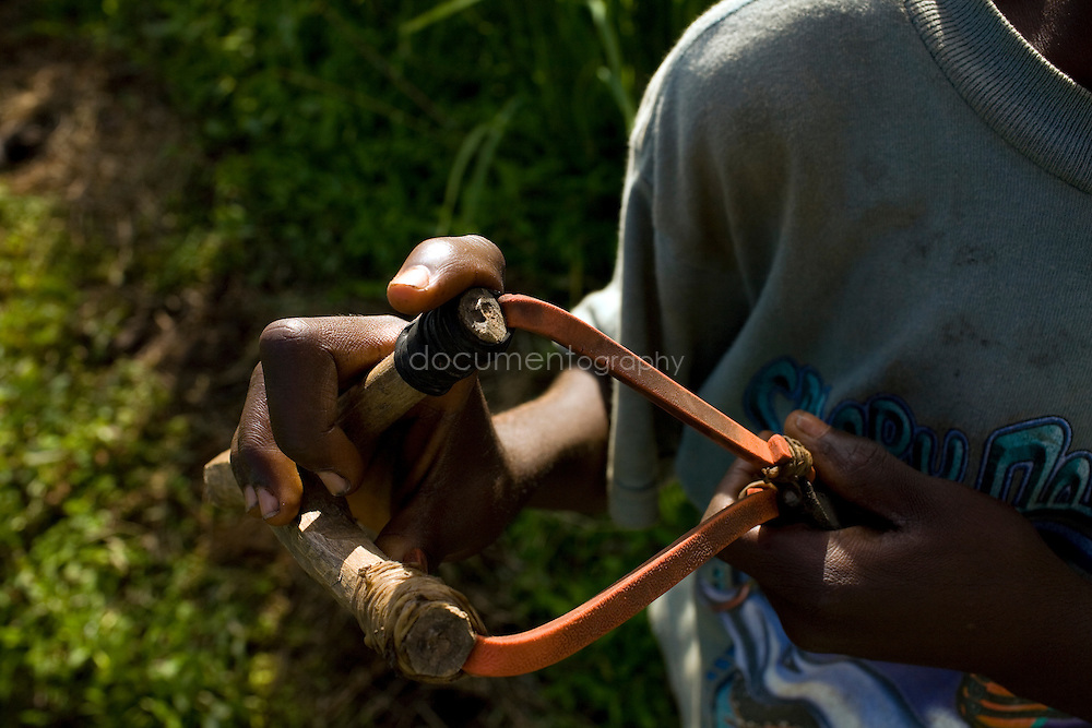 A child holds a sling to chase birds in the rice fields, Kingsville #7, Liberia.