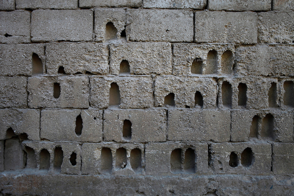 A yard wall in Koreen sprayed with holes caused by heavy fighting.<br /> _ _ _ <br /> Idlib Interim - Challenging life without central government in the village of Koreen (Idlib Province, Syria)<br /> Koreen joint the syrian uprisung to ouster president Bashar al-Assad at a very early stage in 2011. It has been scene of Army attacks and heavy shelling since 2012. In the course of the fightings the village of a few thousend inhabitants was almost abandoned as barrel bomb campaings commited by the regime pounded Koreen. But since regime forces retreated to few bases remaining in Idlib province people returned home to establish a new and almost unregulated economic, social and community life. The regimes power has no affect and can&acute;t reach them anymore. On the other hand a new government isn&acute;t established yet and not in sight at all. Koreen is free to make its way.