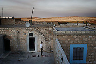 Syria. A Syrian man prays on the roof top of his house at sunset in a village in Aleppo's province. ALESSIO ROMENZI