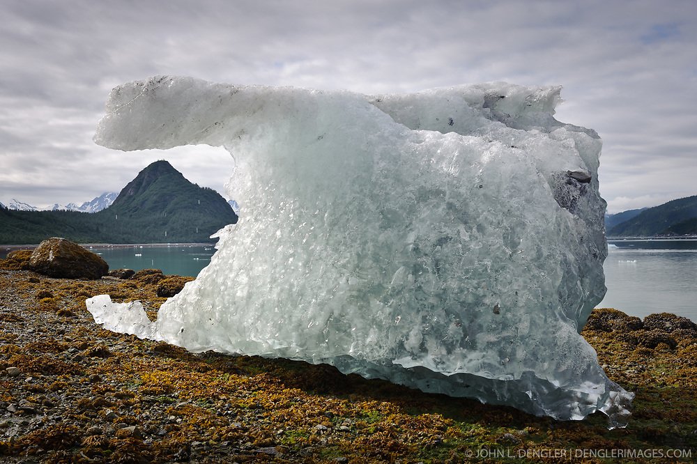 "An iceberg from the McBride Glacier is stranded on a Muir Inlet beach during low tide near Van Horn Ridge. In the background is ""The Nunatak."" Muir Inlet is located in Glacier National Park and Preserve in southeast Alaska."