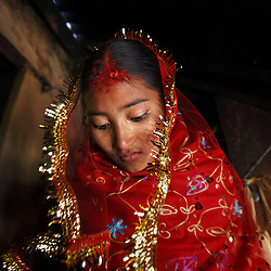 Sumeena, 15, leaves her home to meet her groom, Prakash, 16, in Kagati Village, Kathmandu Valley, Nepal on Jan. 24, 2007. The harmful traditional practice of early marriage is common in Nepal. The Kagati village, a Newar community, is most well known for its propensity towards this practice. Many Hindu families believe blessings will come upon them if marry off their girls before their first menstruation.