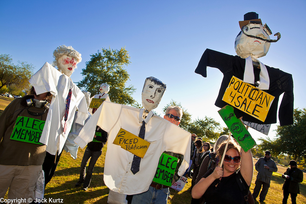 30 NOVEMBER 2011 - PHOENIX, AZ:    Anti-ALEC protesters perform with puppets in a Phoenix park Wednesday. About 300 people picketed the American Legislative Exchange Council (ALEC) conference at the Westin Kierland Resort and Spa in Phoenix, AZ, Wednesday. The protesters claim ALEC, a conservative think tank, violates its tax exempt status by engaging in lobbying, a charge ALEC officials deny. Many conservative pieces of legislation, like Arizona's anti-immigration bill SB1070, originate with ALEC conferences (SB 1070 originated at an ALEC conference several years ago). Many of the protesters are also members of the Occupy movement.     PHOTO BY JACK KURTZ