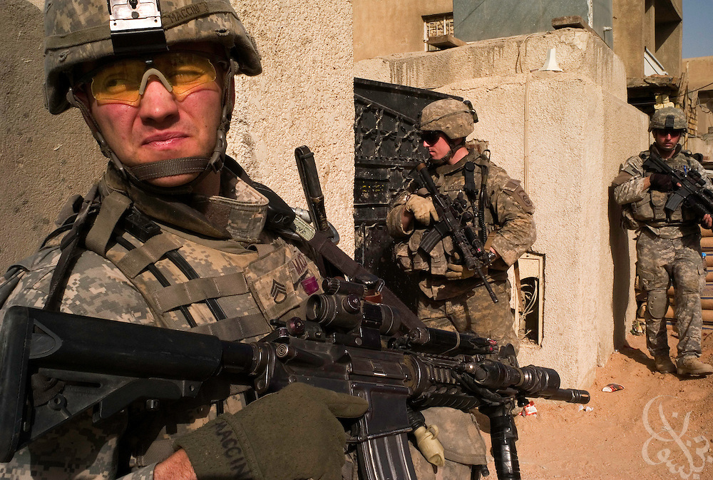 "U.S. Army Sgt. Richard Maccini (left) stands guard as fellow 82nd Airborne Division, 1-73 Cavalry soldiers move in to search a home during a patrol in the Sadr City district of Baghdad, Iraq June 03, 2007. Across Baghdad, the ""Surge"" of U.S. forces enters it's fifth month with mixed results. .."