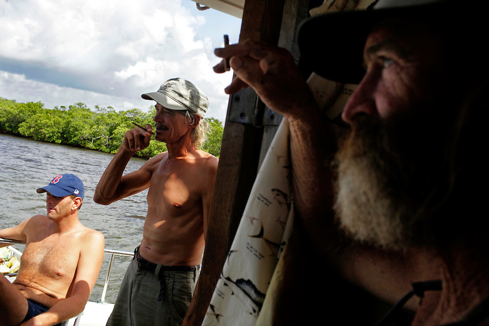 Kenny Canaday, left, Scot Janikula, center, and Randy Eibler, right, watch a Lee County Sheriff's boat pass by as they hang out on Labor Day. Janikula and Eibler are not fans of the Lee County Sheriff deputies, who Eibler says perform constant searches on their vessels just to hassle them.