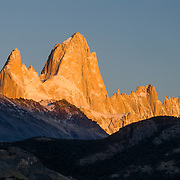 """A golden sunrise spotlights Mount Fitz Roy (3405 meters or 11,170 feet), which rises abruptly on the border between Argentina and Chile in the Southern Patagonian Ice Field in the Andes mountains, near El Chaltén village, in Los Glaciares National Park, Argentina, South America. In 1877, explorer Perito Moreno named """"Cerro Fitz Roy"""" for Robert FitzRoy (no space before the capital R) who, as captain of the HMS Beagle, had travelled up the Santa Cruz River in 1834 and charted much of the Patagonian coast. First climbed in 1952 by French alpinists Lionel Terray and Guido Magnone, Mount Fitz Roy has very fickle weather and is one of the world's most challenging technical ascents. It is also called Cerro Chaltén, Cerro Fitz Roy, and Monte Fitz Roy (all with a space before the R). Chaltén comes from a Tehuelche (Aonikenk) word meaning """"smoking mountain"""" (explained by frequent orographic clouds). Cerro is a Spanish word meaning hill. El Chaltén village was built in 1985 by Argentina to help secure the disputed border with Chile, and now tourism supports it, 220 km north of the larger town of El Calafate. The foot of South America is known as Patagonia, a name derived from coastal giants, Patagão or Patagoni, who were reported by Magellan's 1520s voyage circumnavigating the world and were actually Tehuelche native people who averaged 25 cm (or 10 inches) taller than the Spaniards. Mount Fitz Roy is the basis for the Patagonia company's clothing logo, after Yvon Chouinard's ascent and subsequent film in 1968."""