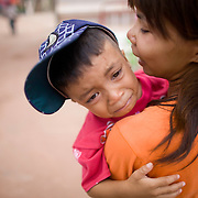 A frightened Thai boy clings to his mother during festivities at Thailand's Phi Ta Khon Ghost festival Friday, June, 22nd, 2012, in Dan Sai, Thailand.  The Dan Sai Ghost Festival is unique to the Isan area of Thailand in the east and is part of local beliefs in spirits and ghost and is also a Buddhist merit making festival.  The ghost masks are made from bamboo sticky rice cookers and the costumes usually strips of cloth sewn together.  The origins of the Phi Ta Khon Festival are said to come from Buddha's last great incarnation before attaining Enlightenment.
