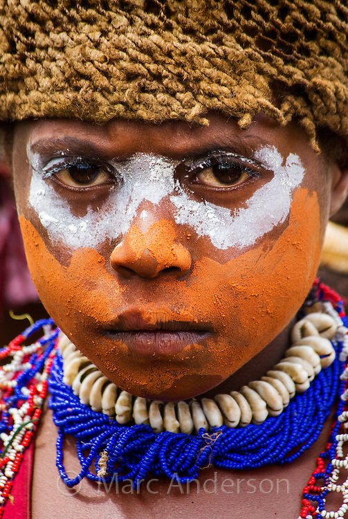 Young boy with his face painted orange and white, wearing a traditional red feather headdress and a blue necklace of seashells. Goroka Festival in the highlands of Papua New Guinea.