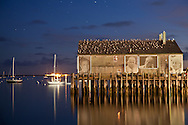A time exposure of Fisherman's Wharf in Provincetown Harbor.  The photographs on the side of the building are of fishermens' wives.