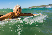 Woman surfer paddling her surfboard in the surf, Sandy Beach, Coffs Harbor, NSW, Australia