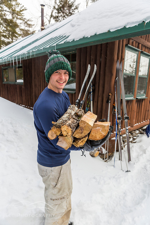 A man with an arm load of fire woods outside Haskell Hut in Maine's Katahdin Woods and Waters National Monument.