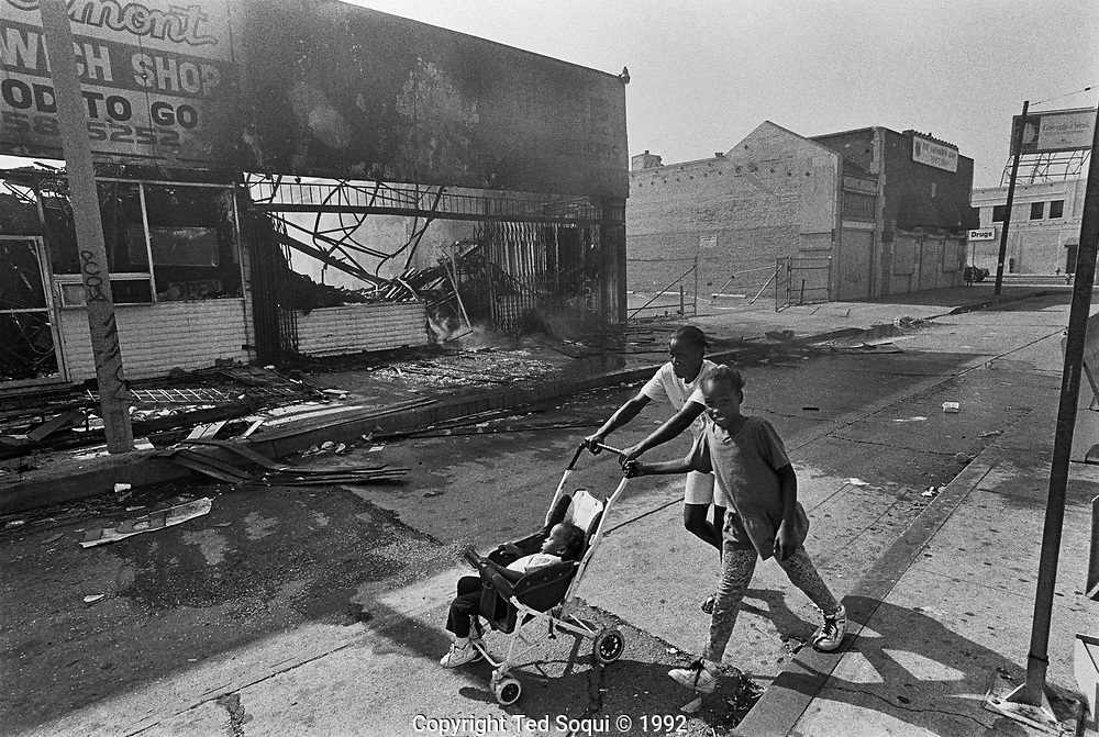 A woman pushing a stroller with her daughter on Vermont Ave and 86th in South Central Los Angeles. <br /> Los Angeles has undergone several days of rioting due to the acquittal of the LAPD officers who beat Rodney King.<br /> Hundreds of businesses were burned to the ground and over 55 people have been killed.