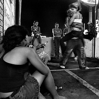 A group of child prostitues joke around with a group of guys along a main street in downtown Managua, Nicaragua.