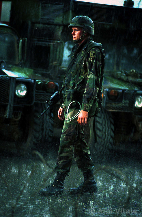An American NATO soldier stands in the pouring rain protecting Serb civilians from ethnic Albanians who forced them out of their homes Wednesday, June 30, 1999 in Urosevac in Kosovo. (Photo by Ami Vitale)