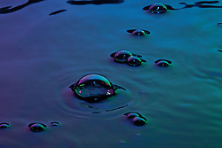 Multicolor large bubbles emerge on the surface of a reflecting water surface