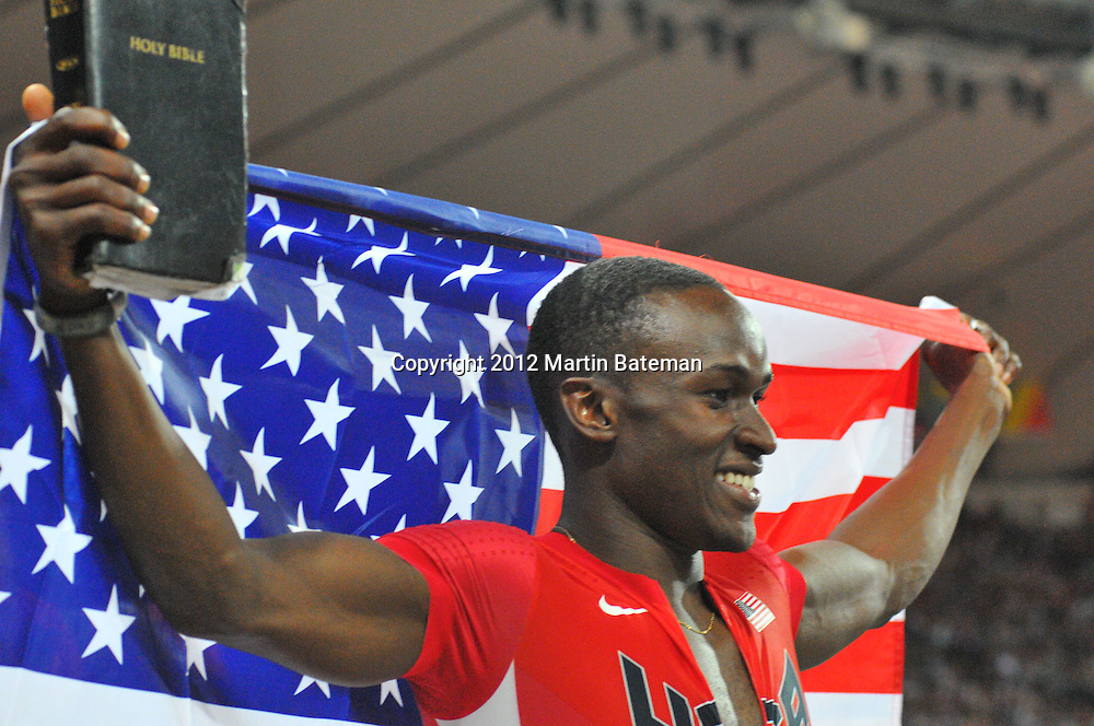 Will Claye carries a bible with the US flag on his lap of honour after winning bronze in the men's long jump, 4th August 2012 at the London Olympics
