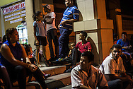 SAN PEDRO SULA, HONDURAS - MAY 23, 2014:  Travelers wait to catch a bus from San Pedro Sula, Honduras to Guatemala City, Guatemala. The manager of the bus line estimated over 80 percent of this route's passengers are migrants headed north, trying to enter the United States illegally. PHOTO: Meridith Kohut for The New York Times