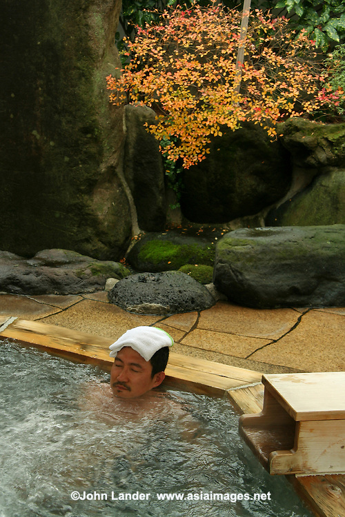 "Yajikitanoyu Onsen, Hakone - A man relaxing at an open air hot spring called a ""rotemburo"" in Japan.  Bathing in a natural atmosphere, among the trees and under open skies, is a favorite with Japanese."
