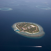 Aerial view of a passing boat and one of 1,192 coral  inhabited and deserted islands in the Islamic Republic of Maldives.