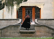 Armed caped red head woman climbing steps to haunted house Jekyll Island