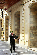 A police officer reaches for his pocket as he passes by a commercial street in downtown. Azeri GDP grew 41.7% in the first quarter of 2007, possibly the highest of any nation worldwide, as the country economy completed its post-Soviet transition into a major oil based economy.<br /> Baku was awarded the right to host of the first European Games, a multi-sport event.