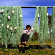 Grant Meanus, 10, swings on his uncle's fishing net set out for drying, he a member of the Celilo Indian tribe on their reservation in Celilo, Oregon.