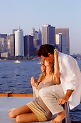 couple kissing while on the back of a boat in the Hudson River in New York City