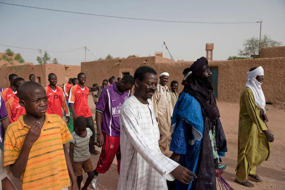 Mohamed aka Boss walking in Agadez' streetwith his football team and some of his associates. He is going to a football match he organised . The footballers are migrants from his own ghetto :  migrants from Mali versus migrants from Burkina Faso.