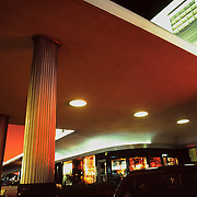 Covered entrance of the parking lot. River Oaks Shopping Center in Houston, Texas at sunset. The sky is orange. Shop windows are brightly lit. Two fluted columns are details of this fine of Art Deco architecture.