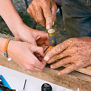 Boy working with Andy Mackie to  make a guitar at an Andy Mackie Music Foundation event during the 2009 American Fiddle Tunes Festival at Fort Worden in Port Townsend, Washington.